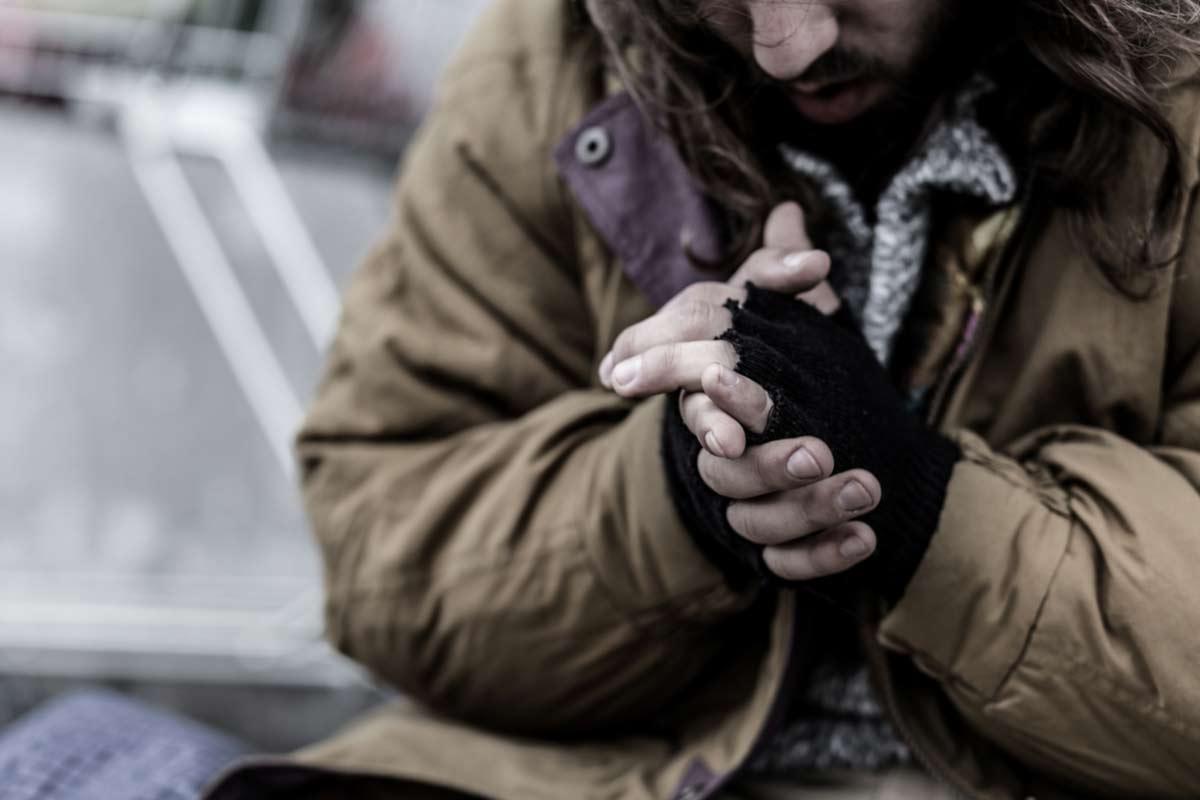 Mann mit zerschlissenen Handschuhen