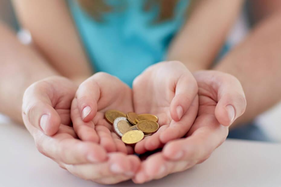 Mutter und Tochter halten Kleingeld in der Hand