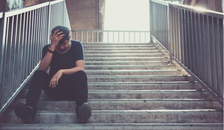 Trauriger Mann sitzt auf einer Treppe