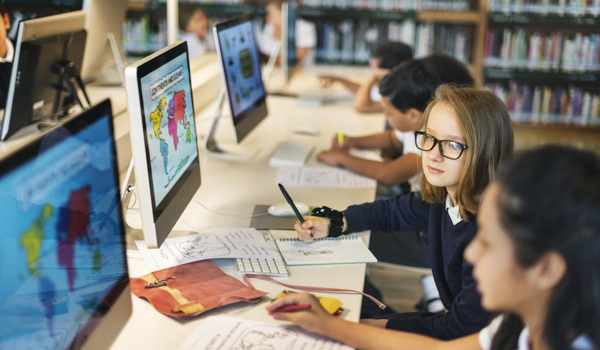Kinder sitzen in der Schule vor Computern