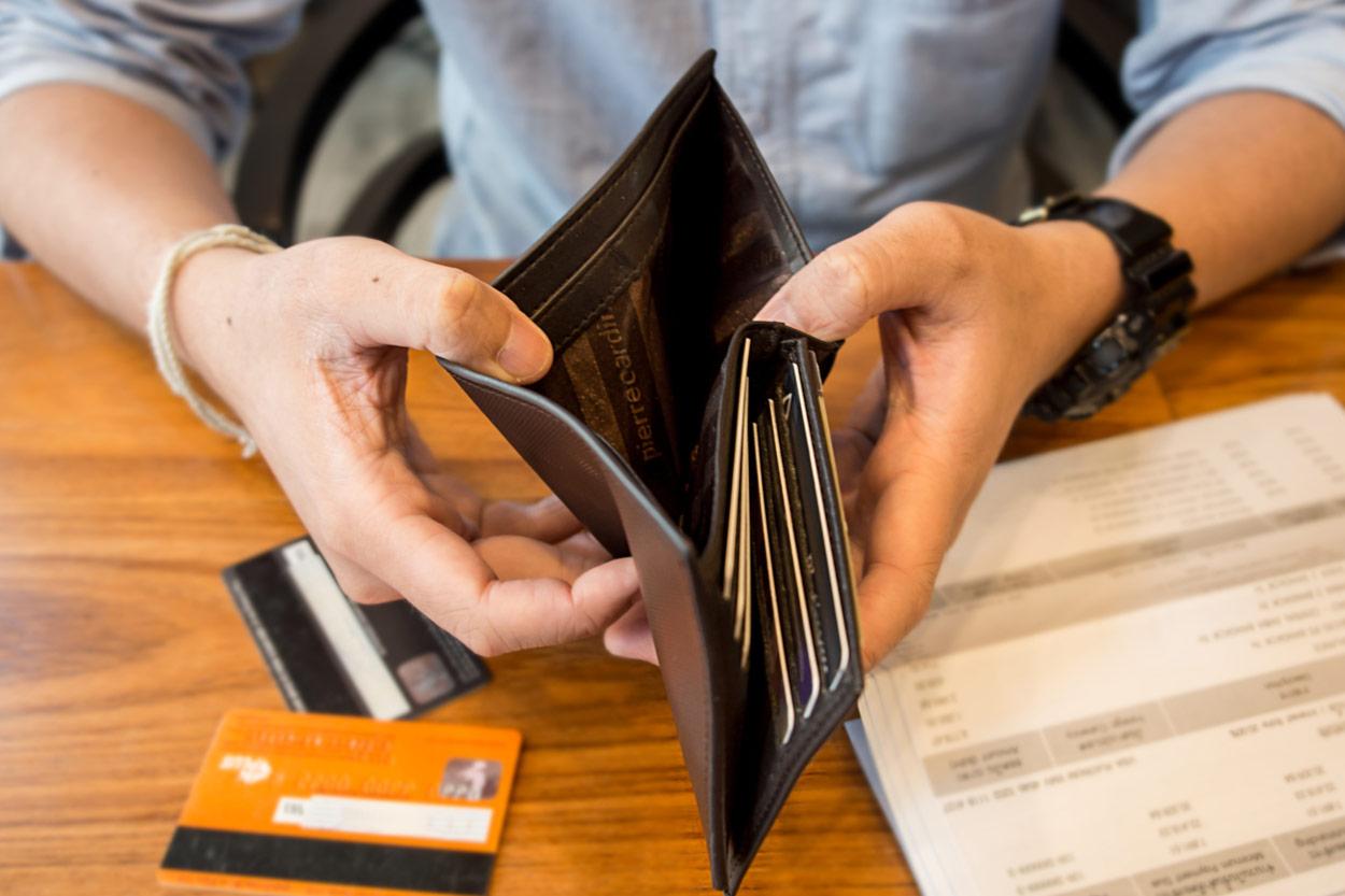 Mann hält leere Geldbörse und sitzt an einem Tisch