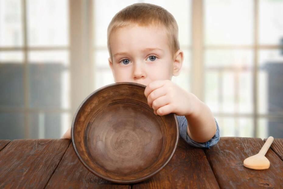 Kleiner Junger zeigt seinen leeren Teller