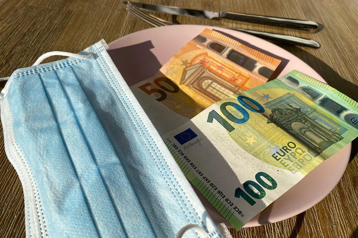 150 Euro auf leerem Teller mit Covid19 Mund-Nasen-Bedeckung