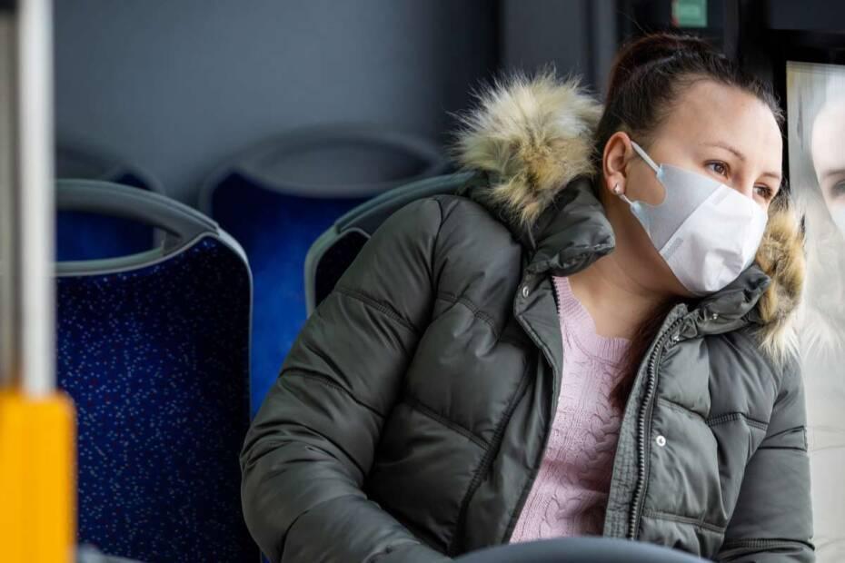 Frau sitzt mit Maske im Bus