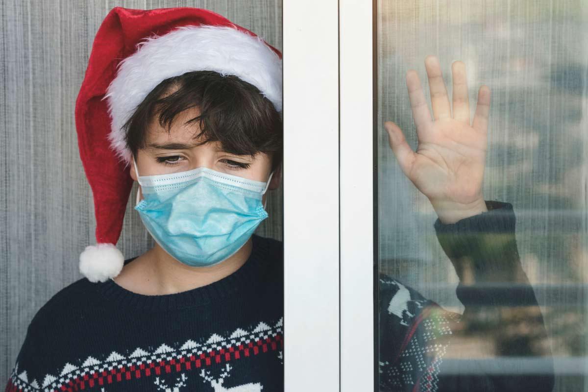Trauriges Kind an Weihnachten mit Corona-Maske
